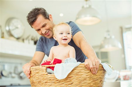 Father carrying baby in laundry basket Stock Photo - Premium Royalty-Free, Code: 6113-07242888