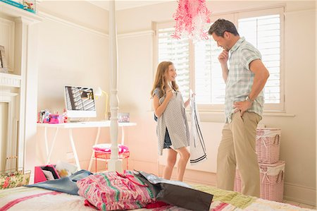 Father helping daughter pick clothing Stock Photo - Premium Royalty-Free, Code: 6113-07242891