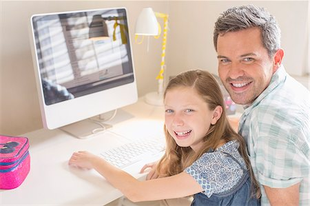 Father and daughter using computer together Stock Photo - Premium Royalty-Free, Code: 6113-07242899