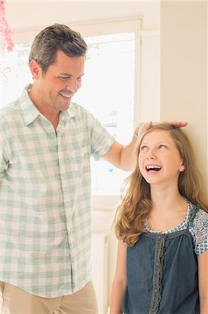 female hand - Father measuring daughter's height on wall Stock Photo - Premium Royalty-Free, Code: 6113-07242811
