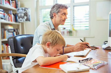 Father and son working in home office Stock Photo - Premium Royalty-Free, Code: 6113-07242819
