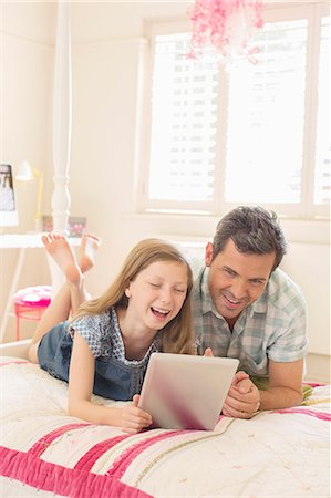 elementary age - Father and daughter using digital tablet on bed Stock Photo - Premium Royalty-Free, Code: 6113-07242831