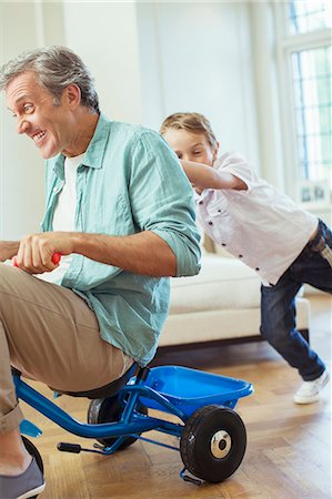 Boy pushing father on tricycle indoors Stock Photo - Premium Royalty-Free, Code: 6113-07242962