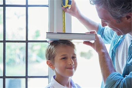 Father measuring son's height on wall Stock Photo - Premium Royalty-Free, Code: 6113-07242973