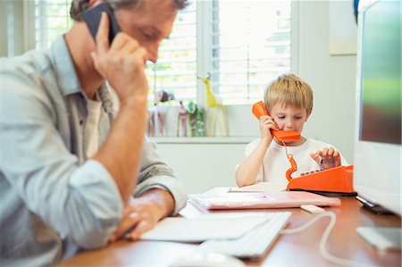 Father and son working in home office Stock Photo - Premium Royalty-Free, Code: 6113-07242984