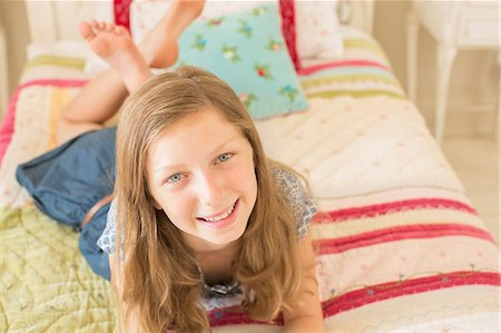 Smiling girl laying on bed Stock Photo - Premium Royalty-Free, Code: 6113-07242902
