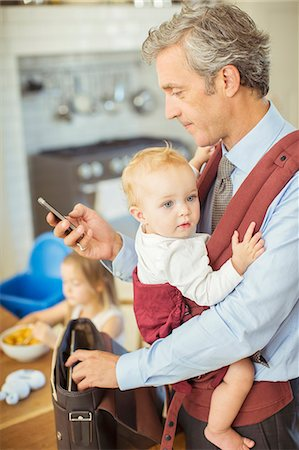 Father holding baby and checking cell phone Stock Photo - Premium Royalty-Free, Code: 6113-07242914