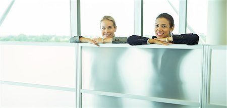Smiling businesswomen leaning against half wall in office Stock Photo - Premium Royalty-Free, Code: 6113-07243057