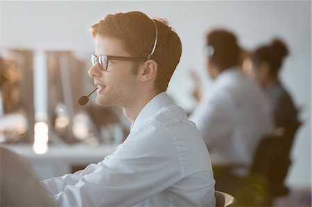 Businessman wearing headset in office Stock Photo - Premium Royalty-Free, Code: 6113-07243059
