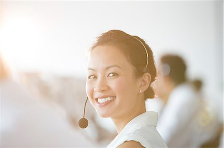 release - Businesswoman wearing headset in office Stock Photo - Premium Royalty-Free, Code: 6113-07243066