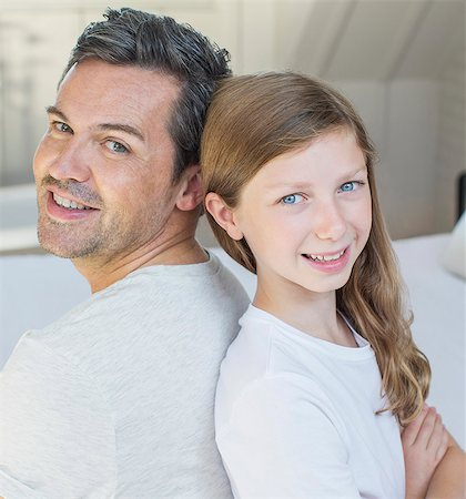 Father and daughter smiling in bedroom Stock Photo - Premium Royalty-Free, Code: 6113-07243018