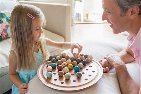 Father and daughter playing Chinese checkers Stock Photo - Premium Royalty-Free, Code: 6113-07243027