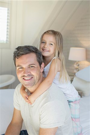 Father and daughter hugging on bed Stock Photo - Premium Royalty-Free, Code: 6113-07243029