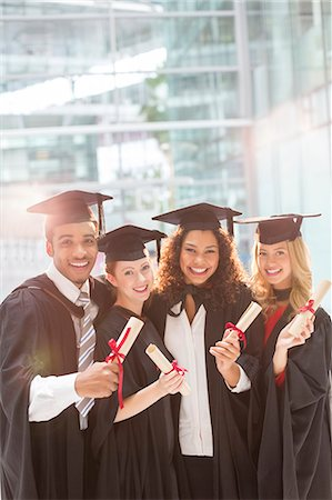 Smiling graduates holding diplomas Stock Photo - Premium Royalty-Free, Code: 6113-07243346