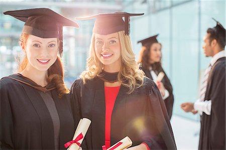 Smiling graduates holding diplomas Stock Photo - Premium Royalty-Free, Code: 6113-07243378