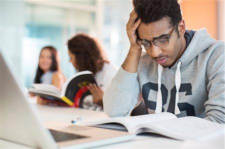 University student reading in classroom Stock Photo - Premium Royalty-Free, Code: 6113-07243394