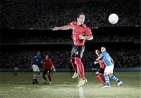 Soccer player jumping on field Stock Photo - Premium Royalty-Free, Code: 6113-07310547