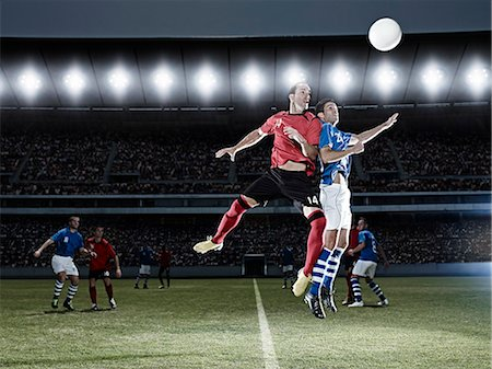 Soccer players jumping for ball on field Stock Photo - Premium Royalty-Free, Code: 6113-07310544