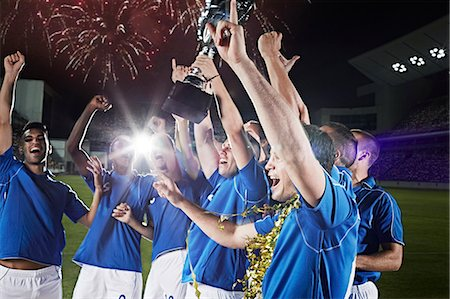 football team - Soccer team cheering with trophy on field Stock Photo - Premium Royalty-Free, Code: 6113-07310553