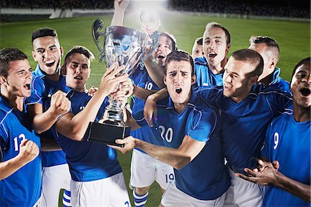 football team - Soccer team cheering with trophy on field Stock Photo - Premium Royalty-Free, Code: 6113-07310558