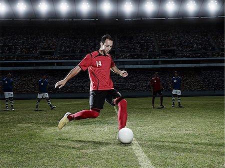 footballeur - Soccer player kicking ball on field Stock Photo - Premium Royalty-Free, Code: 6113-07310563