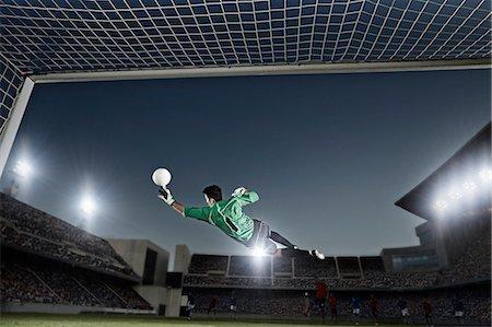 soccer player (male) - Goalie jumping for ball in soccer net Stock Photo - Premium Royalty-Free, Code: 6113-07310571