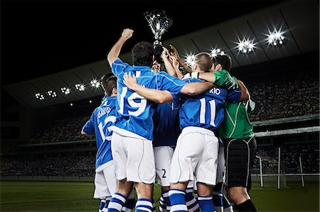 football team - Soccer team cheering with trophy on field Stock Photo - Premium Royalty-Free, Code: 6113-07310578