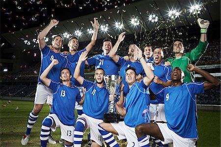football team - Soccer team cheering with trophy on field Stock Photo - Premium Royalty-Free, Code: 6113-07310580