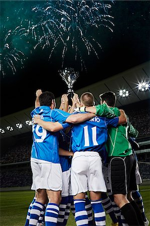 football team - Soccer team cheering with trophy on field Stock Photo - Premium Royalty-Free, Code: 6113-07310581
