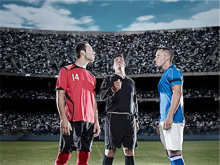 Referee tossing coin in soccer game Stock Photo - Premium Royalty-Free, Code: 6113-07310587