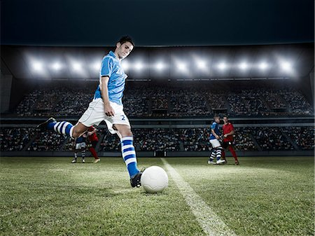 soccer player (male) - Soccer player kicking ball on field Stock Photo - Premium Royalty-Free, Code: 6113-07310538