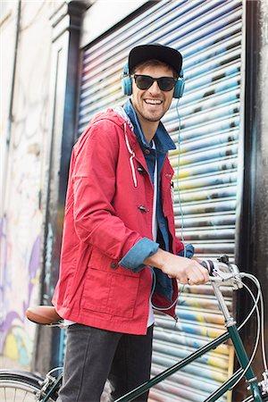 Man pushing bicycle on city street Stock Photo - Premium Royalty-Free, Code: 6113-07542449