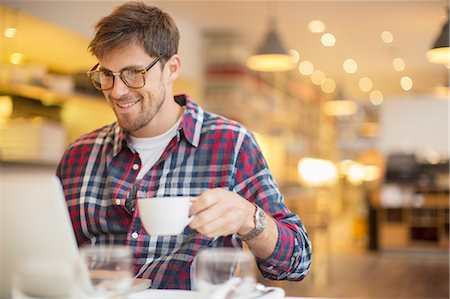 Man using laptop and drinking coffee in cafe Stock Photo - Premium Royalty-Free, Code: 6113-07542425