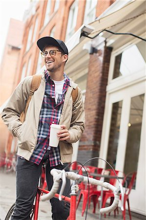 Man drinking coffee on bicycle on city street Stock Photo - Premium Royalty-Free, Code: 6113-07542507
