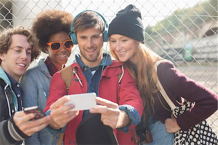 style - Friends taking self-portrait with camera phone outdoors Stock Photo - Premium Royalty-Free, Code: 6113-07542514