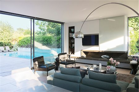 Modern living room overlooking patio with swimming pool Stock Photo - Premium Royalty-Free, Code: 6113-07542672