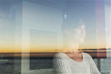 Woman overlooking sunset and ocean from window Stock Photo - Premium Royalty-Free, Code: 6113-07542683