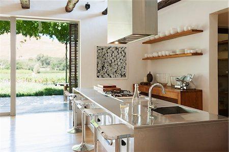 Modern kitchen overlooking patio and vineyard Stock Photo - Premium Royalty-Free, Code: 6113-07542767