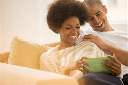 Couple using digital tablet on sofa Stock Photo - Premium Royalty-Free, Code: 6113-07542784
