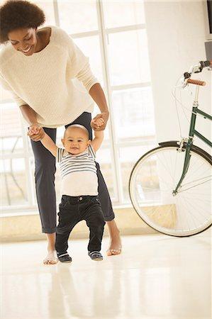 Mother helping baby boy walk in living room Stock Photo - Premium Royalty-Free, Code: 6113-07542842