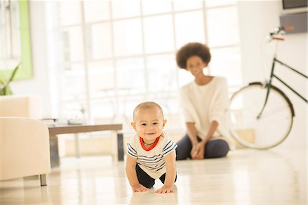 Mother watching baby boy crawl on living room floor Stock Photo - Premium Royalty-Free, Code: 6113-07542864