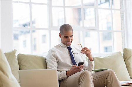 sit - Businessman using cell phone on sofa Stock Photo - Premium Royalty-Free, Code: 6113-07542884