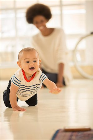 Mother watching baby boy crawl on floor Stock Photo - Premium Royalty-Free, Code: 6113-07542819