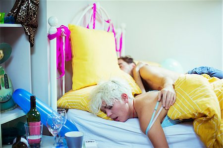Couple sleeping in bed the morning after a party Stock Photo - Premium Royalty-Free, Code: 6113-07542969
