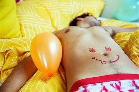 Man with smiley face drawing on belly sleeping after party Stock Photo - Premium Royalty-Free, Code: 6113-07542977