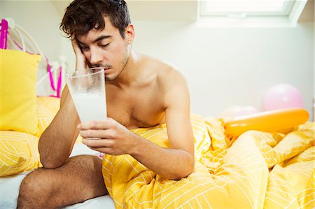 Hungover man drinking concoction in bed the morning after a party Stock Photo - Premium Royalty-Free, Code: 6113-07542982
