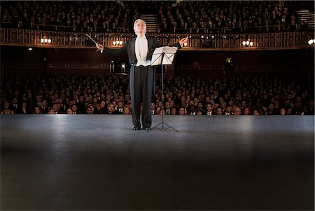 Conductor performing on stage in theater Stock Photo - Premium Royalty-Free, Code: 6113-07542916