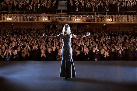 Performer standing with arms outstretched on stage in theater Stock Photo - Premium Royalty-Free, Code: 6113-07542939