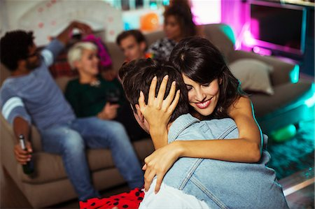 friendship - Couple hugging in living room at party Stock Photo - Premium Royalty-Free, Code: 6113-07543042