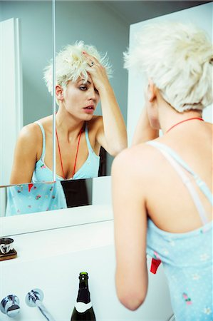 Hungover woman examining herself in mirror Stock Photo - Premium Royalty-Free, Code: 6113-07543000